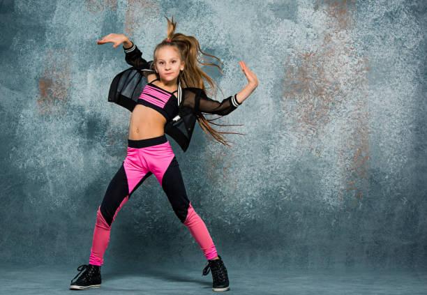 Young girl break dancing on wall background stock photo