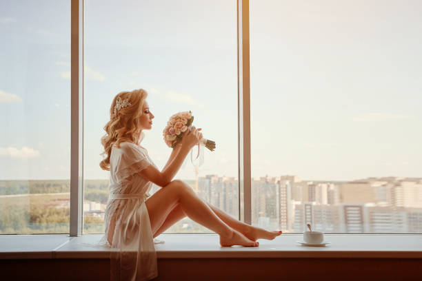 A young girl bride in peignoir sitting on the windowsill with a bouquet. Wedding morning preparation stock photo