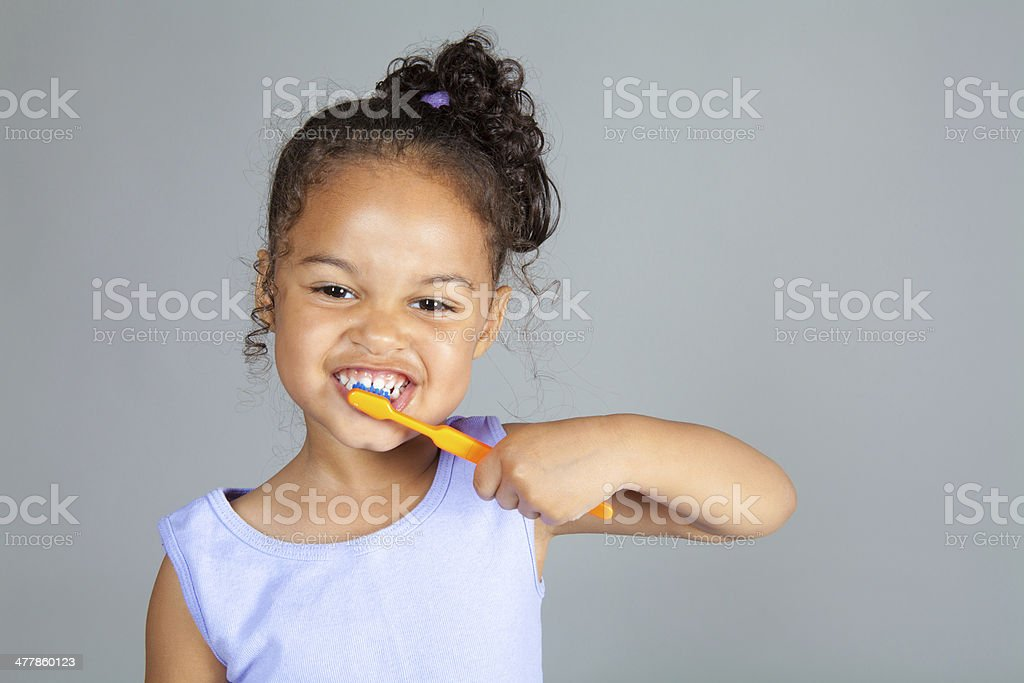 Young girl brushes her teeth stock photo