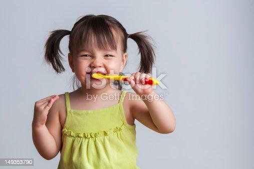 istock Young girl brushing teeth with yellow toothbrush 149353790