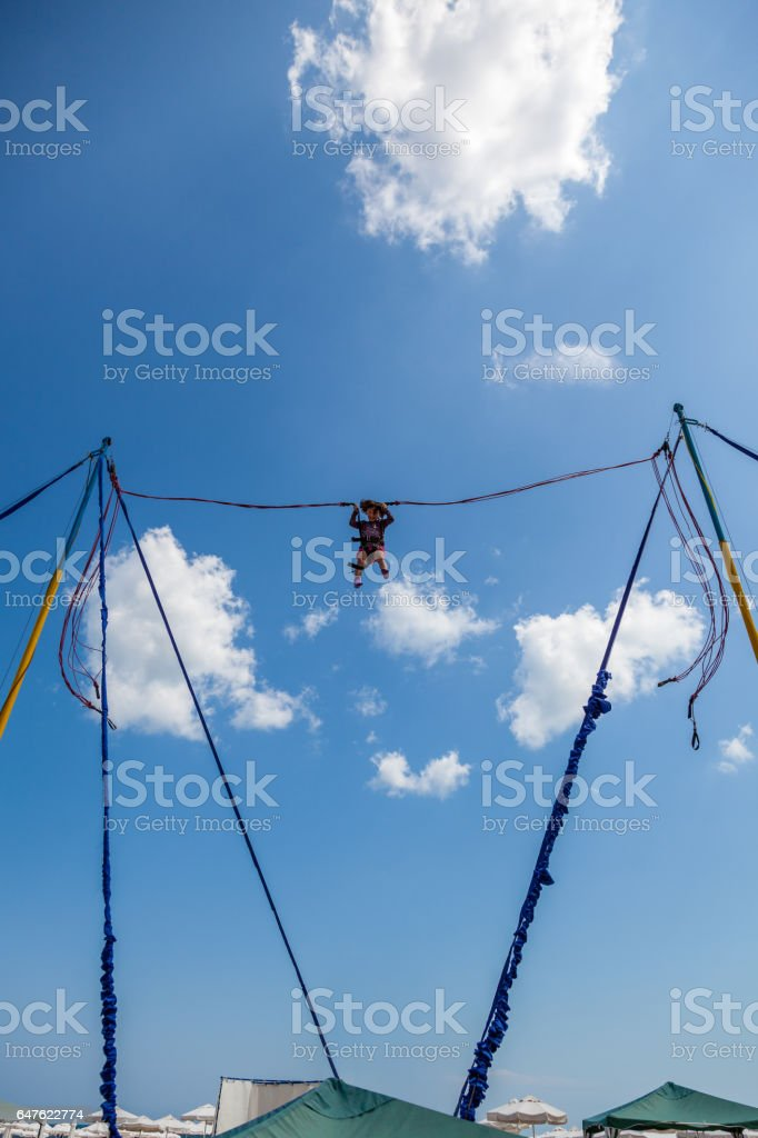 Young girl bungee jump high up in the air. royalty-free stock photo