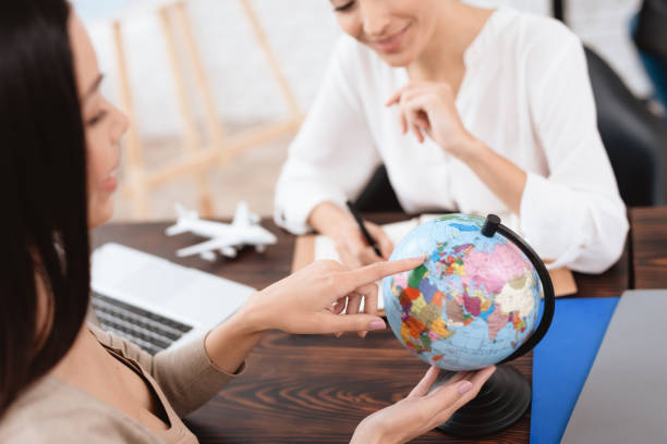 A young girl came to a travel agency. stock photo