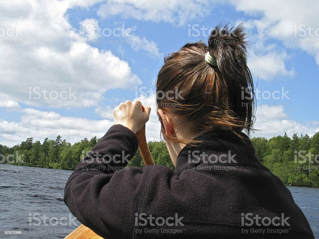Young girl canoeing on big lake in Sweden royalty-free stock photo