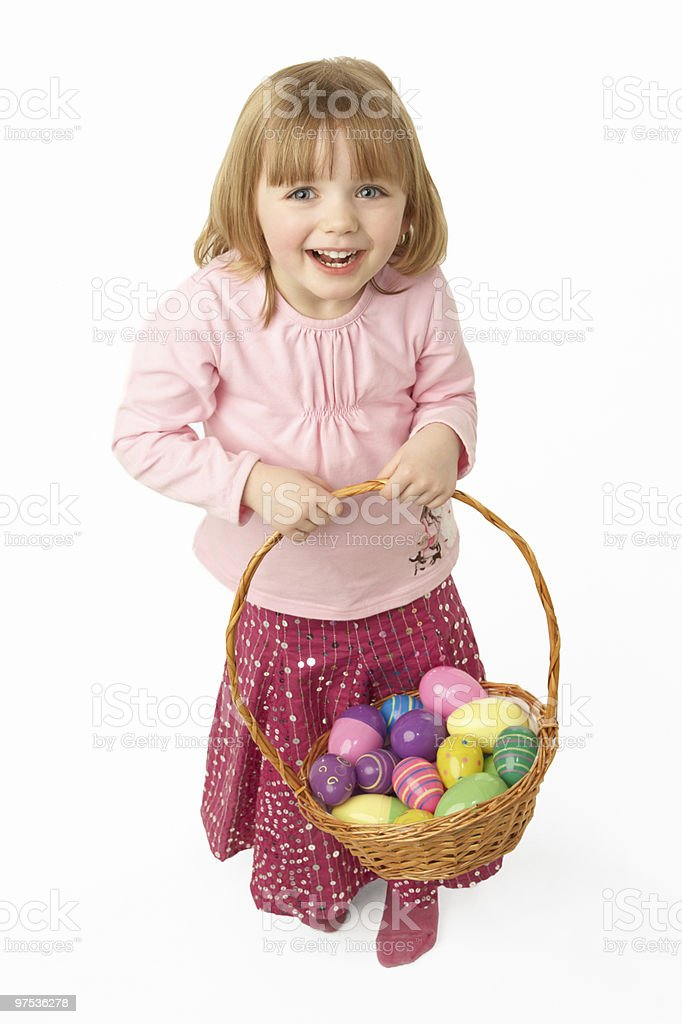 Jeune fille portant un panier rempli d'oeufs de Pâques photo libre de droits