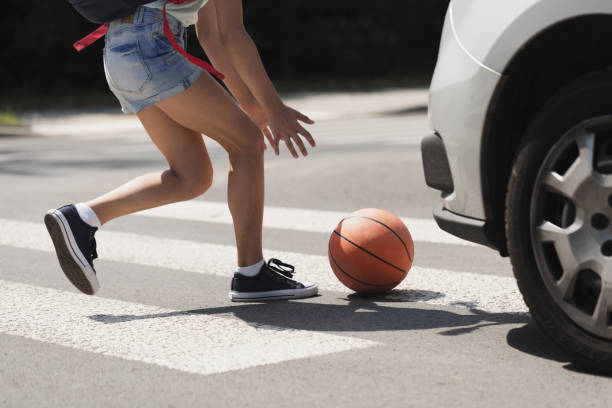 Young girl catching a basket ball on a pedestrian crossing stock photo