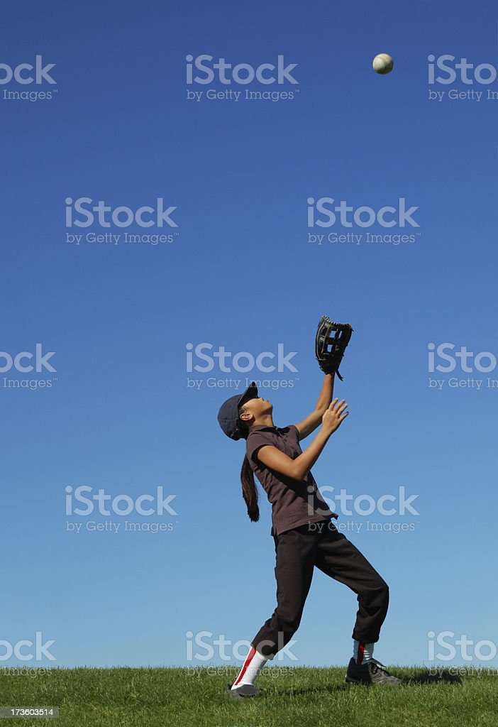 Young girl catching a fly ball stock photo