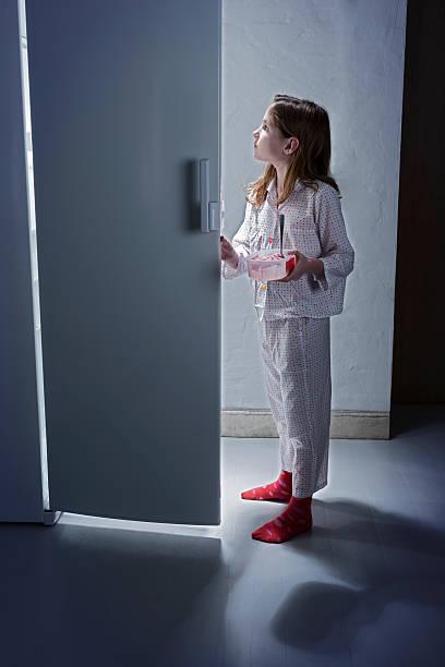 junges mädchen fangen erste snack am späten abend aus dem kühlschrank. - mädchen night snacks stock-fotos und bilder