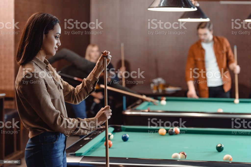 young girl chalking cue beside pool table at bar with friends - Royalty-free Adult Stock Photo