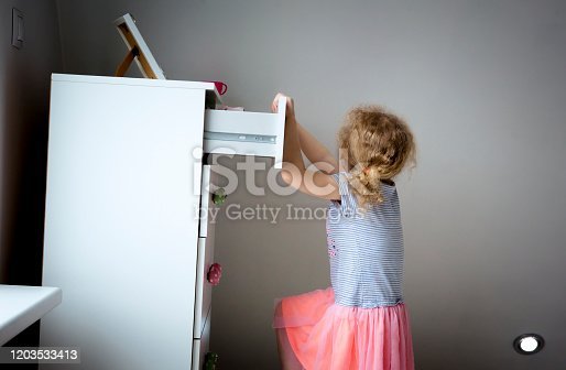 Young girl child climbing on modern high dresser furniture, danger of dresser dipping over concept. Children home hazards. Staged photo.