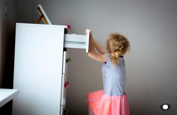현대 높은 드레서 가구에 등반 어린 소녀 아이, 개념을 통해 찍어 드레서의 위험. 어린이 집 위험. 준비 된 사진입니다. - 옷서랍 뉴스 사진 이미지
