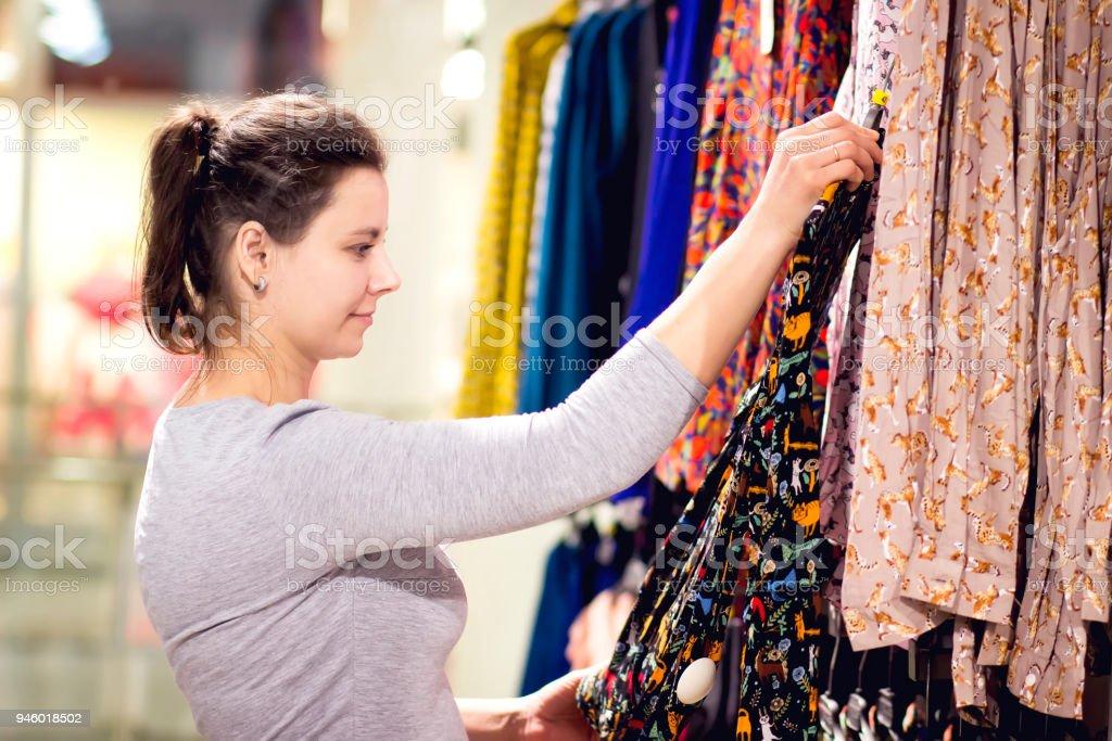 23a2846057bb2 jeune fille choisit le chemisier dans le magasin de vêtements. Jeune femme  caucasienne sur mes
