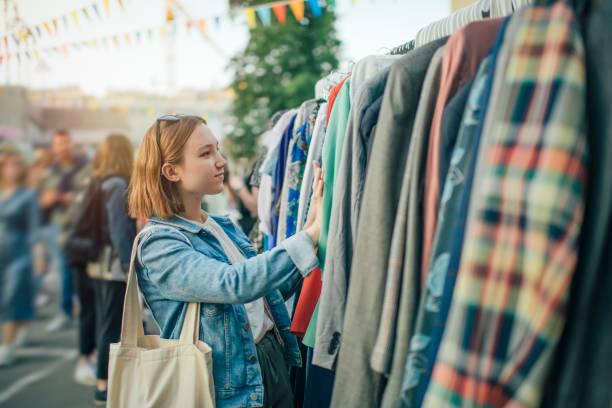 Junges Mädchen wählt Kleidung in einem Second-Hand-Markt im Sommer, Null-Abfall-Konzept – Foto