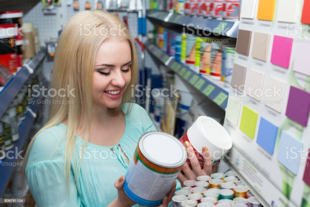 Young girl choosing decorating paint stock photo