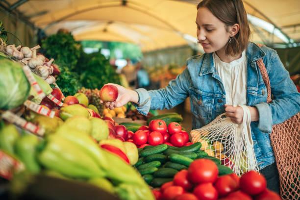 Junges Mädchen, das Gemüse und Obst auf einem Bauernmarkt mit Wiederverwendbaren, plastikfreien und Null-Abfall-Konzept wählt – Foto