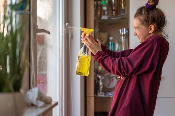 Junges Mädchen putzt Fenster zu Hause – Foto