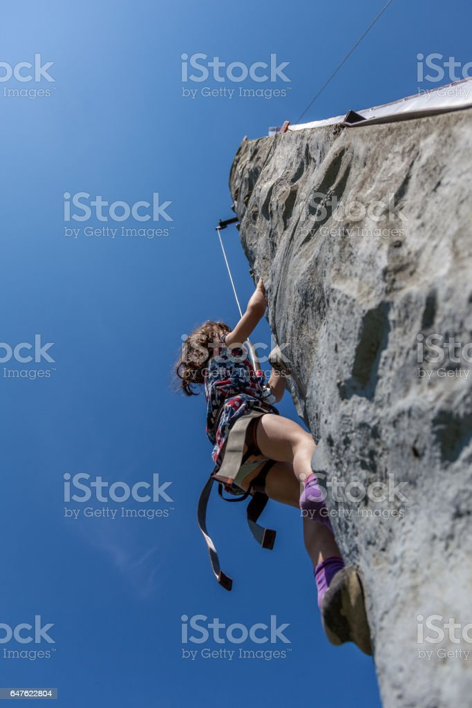 Young girl climbing on vertical wall with ropes outdoors warm summer day with clear blue sky. royalty-free stock photo