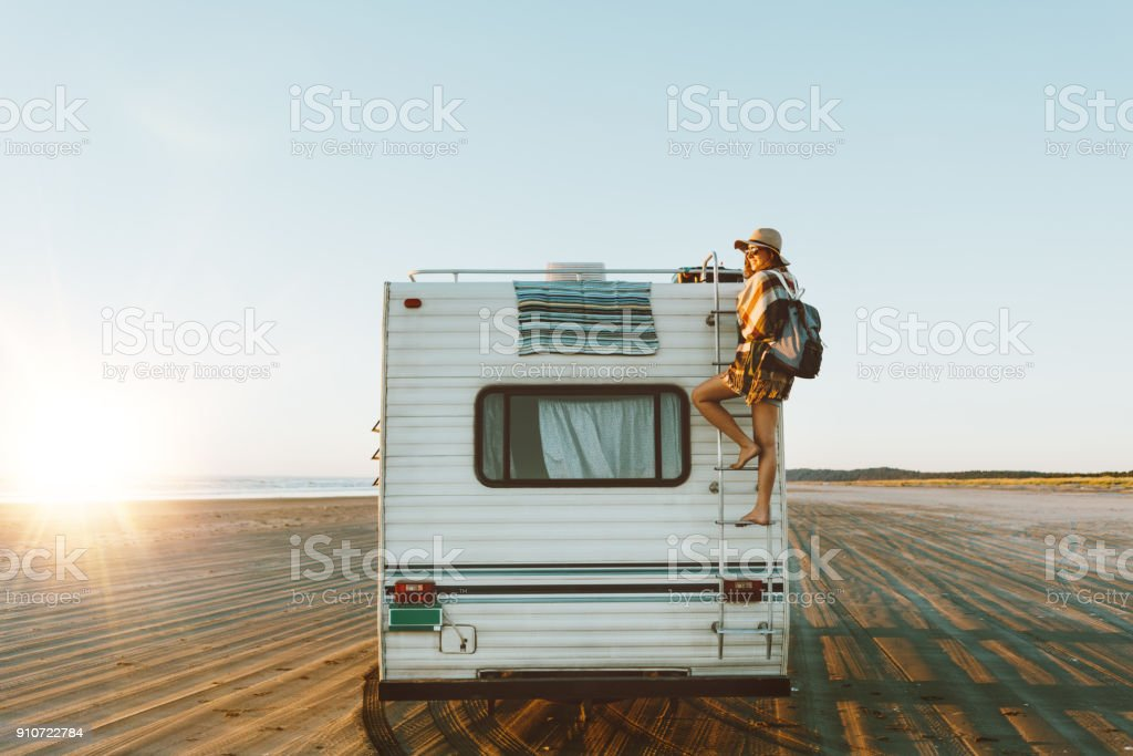 Young girl climbing the top of motorhome stock photo