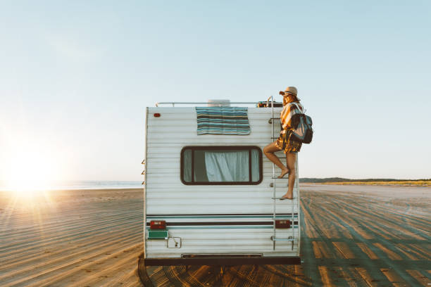 Young girl climbing the top of motorhome Charming young woman with nice smile with hat, sunglasses, backpack climing on recreational vehicle on the ocean beach at sunset. motor home stock pictures, royalty-free photos & images