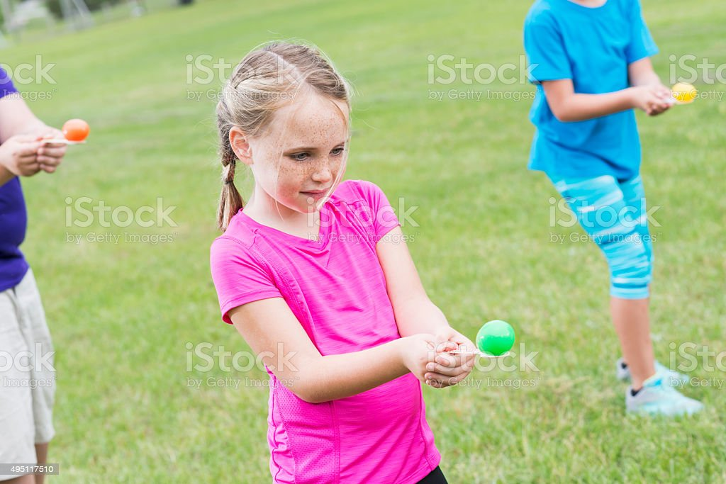 Young girl competing in an egg spoon race stock photo