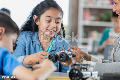 1016655140 istock photo Young girl concentrates while building a robot 964287986