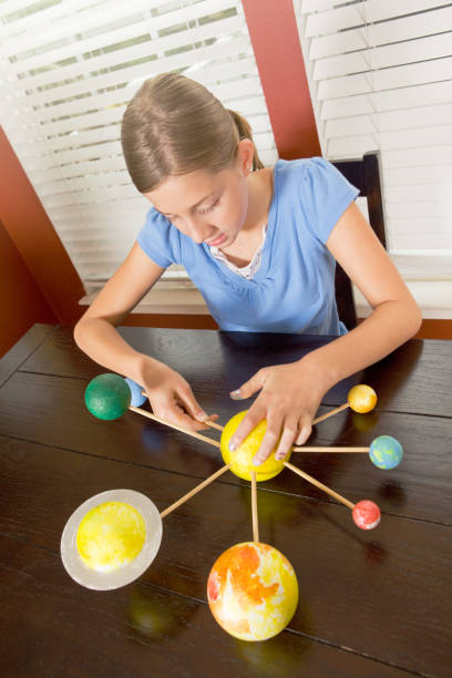 Young Girl Constructing Solar System Model stock photo