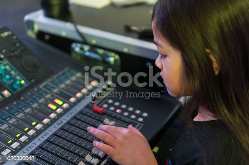 A close-up photograph of a 9-year old eurasian girl controlling a sound mixer desk