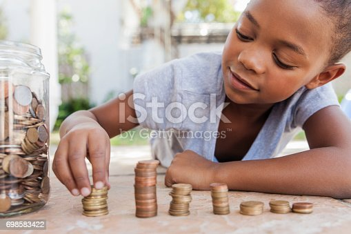 Young african female counting her coins while lying on the floor.