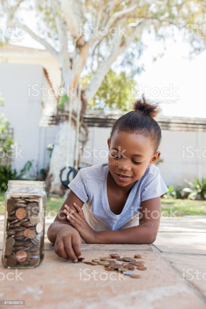 Young girl counting her saved coins. stock photo