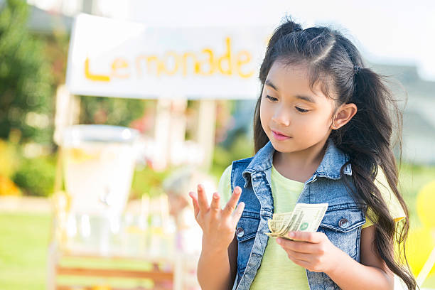 Young girl counts money made from lemonade stand Pretty girl counts on her fingers while holding cash from her lemonade sales. The lemonade stand is in the background. lemonade stand stock pictures, royalty-free photos & images