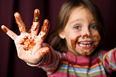 Young girl with chocolate smeared all over her face and fingers. Focus is on mucky hand with face out of focus against a rich red background.