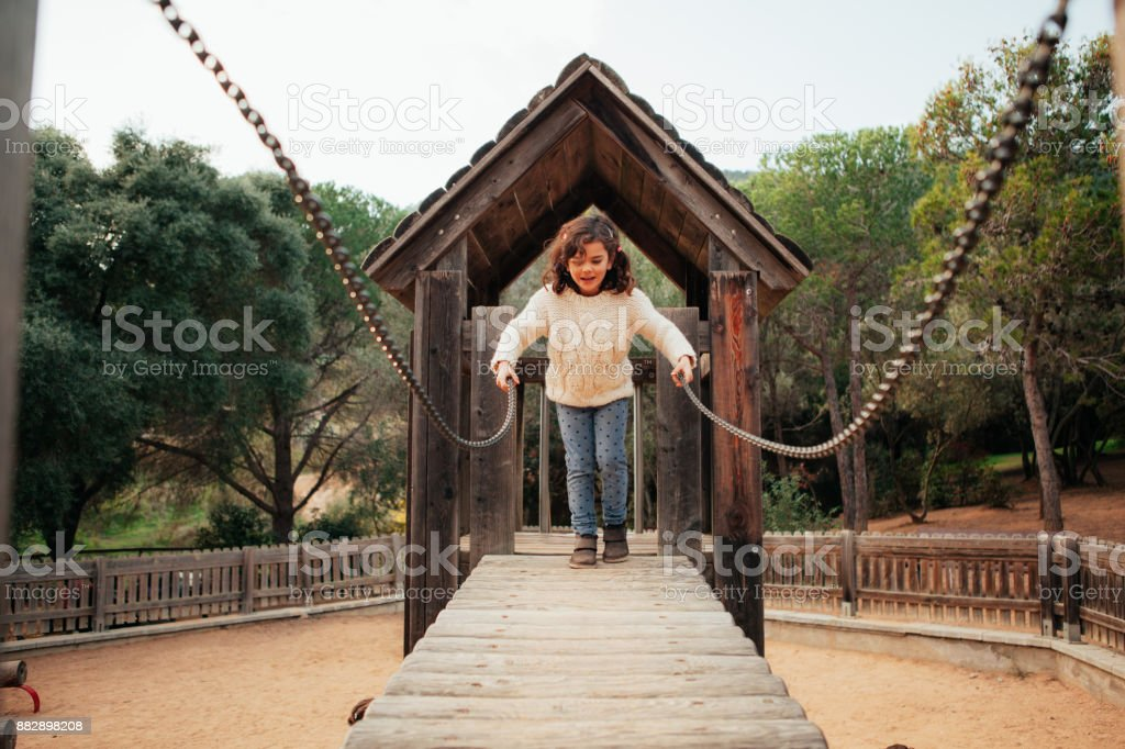 Young girl crossing a bridge stock photo