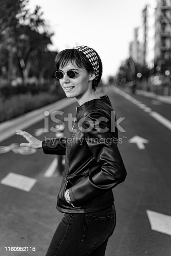 Young girl wearing a black leather jacket, crossing the street in Barcelona, black and white.
