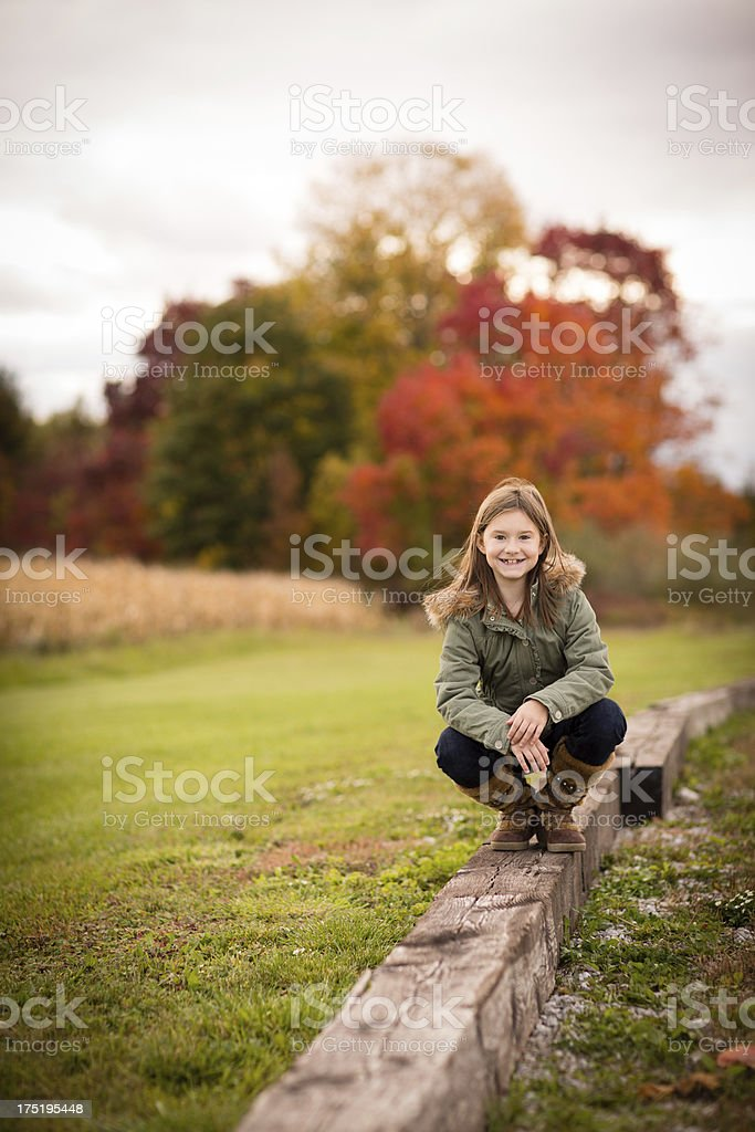 Young Girl Crouching Outside on Railroad Tie in Autumn royalty-free stock photo