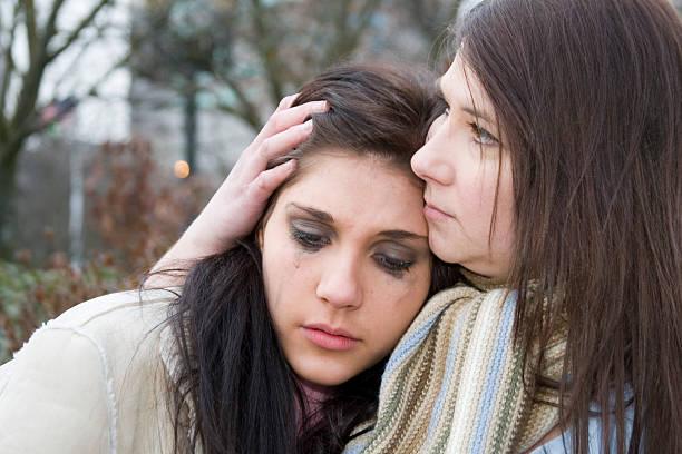 Beautiful Teenage Girl Crying on Moms Shoulder stock photo