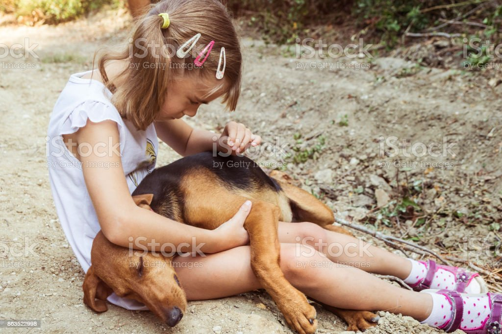 Young girl cuddling her dog on the ground