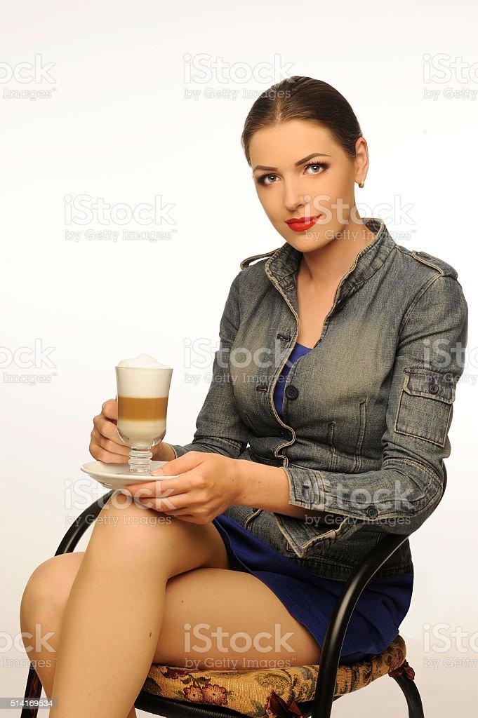Jovem, xícara de capuccino ao lado, área de estar. Belas pernas. - foto de acervo