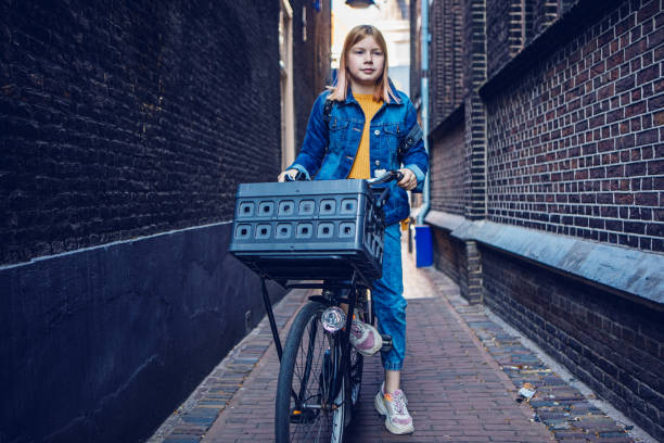 Young girl cycling in an alley stock photo