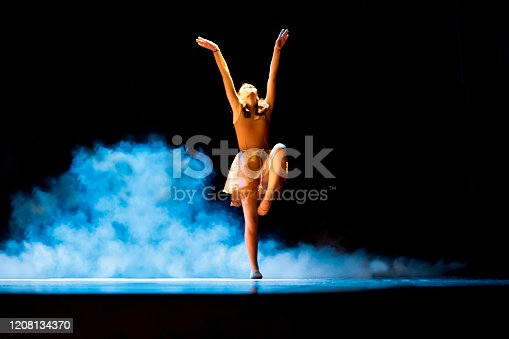 Young girl dancing ballet on a dark stage with blue smoke. Canon Mark IV.