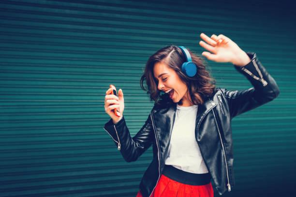 年輕的姑娘跳舞,聽音樂 - 少女 個照片及圖片檔