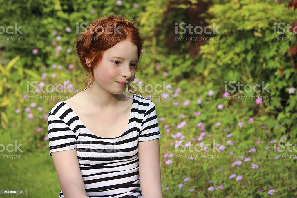 Young girl daydreaming in summer garden, looking down / looking downwards stock photo