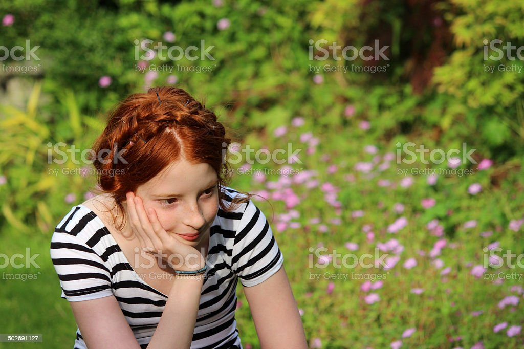 Young girl daydreaming in summer garden, resting head on hand stock photo