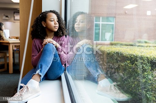The young girl sits on the windowsill at the library as she looks out the window and daydreams.
