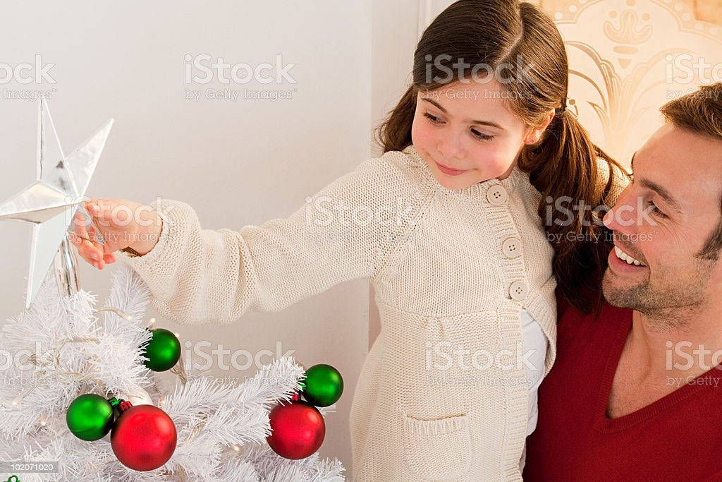 Young girl decorating Christmas tree royalty-free stock photo