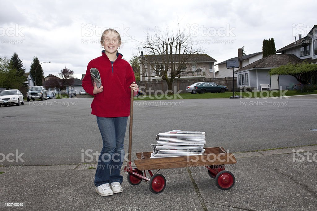 Young girl delivering newspapers with wagon in suburban neighborhood. stock photo