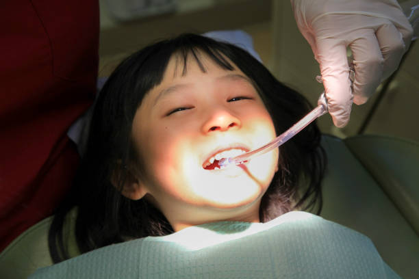 Young Girl Dentist Visit Young Asian girl is having her dental checked by a dentist. suction tube stock pictures, royalty-free photos & images