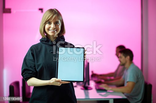 istock Young girl designer stands with tablet with empty screen at the office during developing a new project, pink background 1255193497