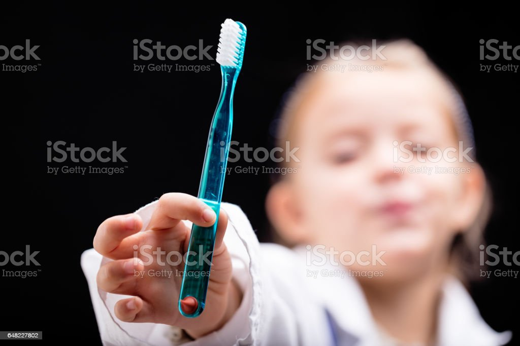 Young girl displaying a toothbrush for the camera stock photo