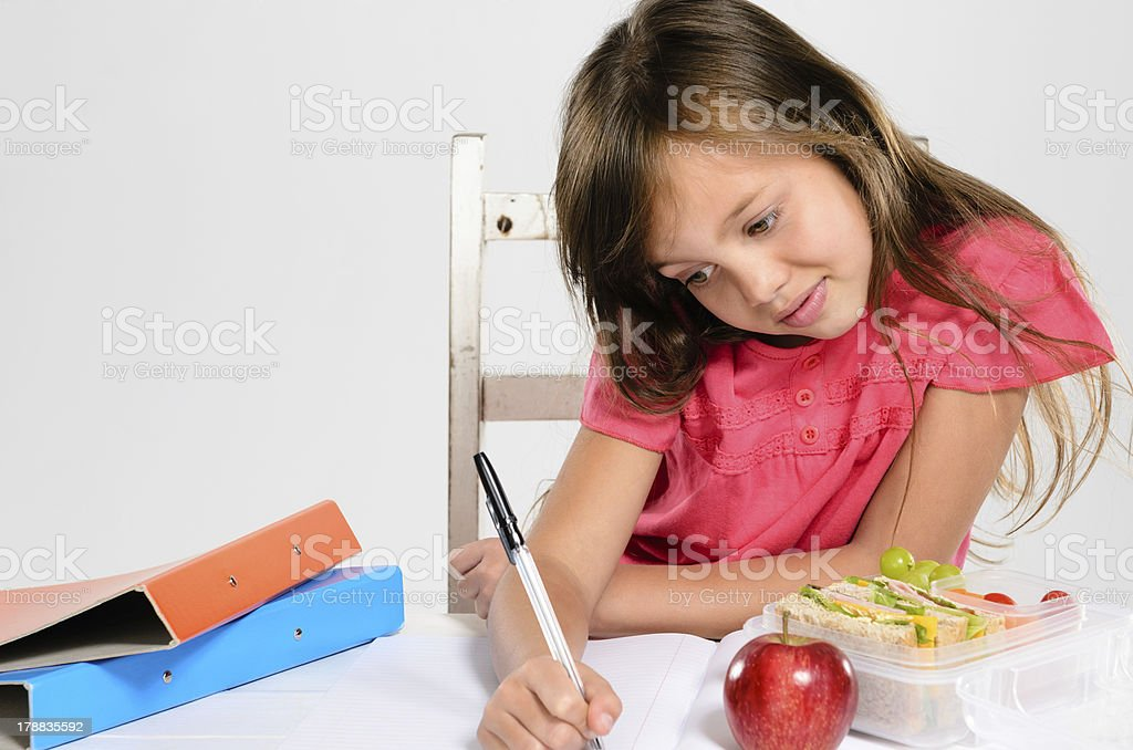 Young girl does her homework on table royalty-free stock photo