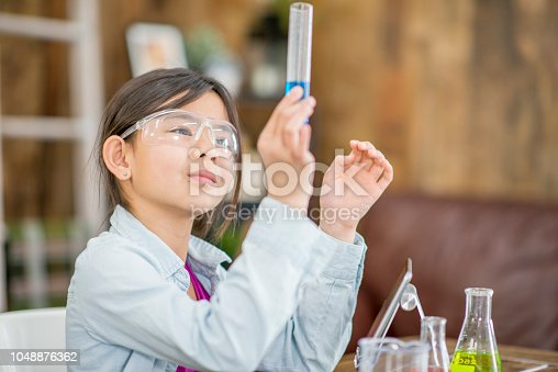 A girl of elementary age looks up at a blue beaker in her hand with intrigue. She is sitting at a desk by herself and has safety glasses on.