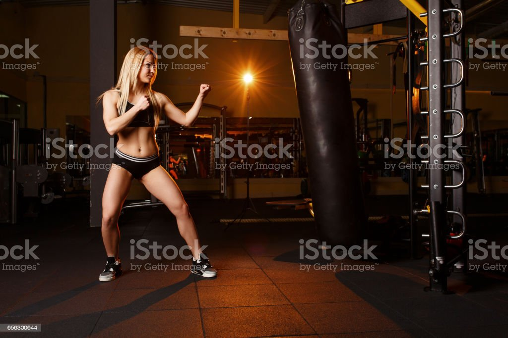 Young girl doing boxing workout in the gym. Female fighter kicking punching bag. stock photo